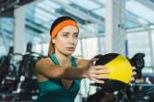 donna sportiva allenamento con palla medica presso palestra