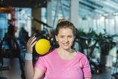 donna sorridente sovrappeso con palla medica sulla spalla