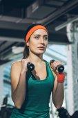 Fotografie sportovní ženu, která cvičí s činkami v posilovně