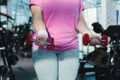 bránice obézní ženy s činkami v posilovně