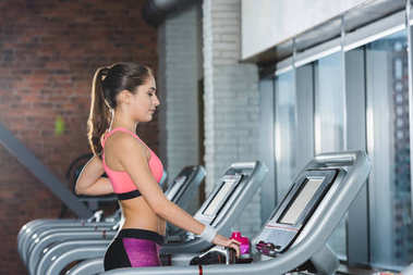 sporty woman standing on treadmill at gym