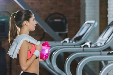 sporty woman with towel and bottle of water standing against treadmill