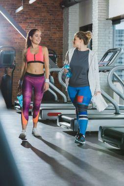 women walking against treadmills at gym