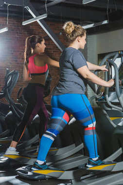 sporty and overweight  women training on treadmills at gym
