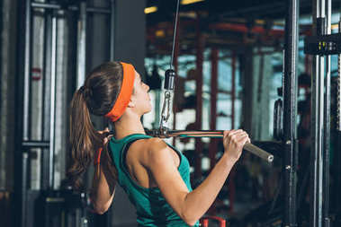 sporty woman training her chest on training apparatus