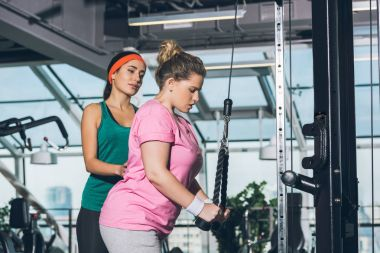 trainer helping to overweight woman while she training on training apparatus