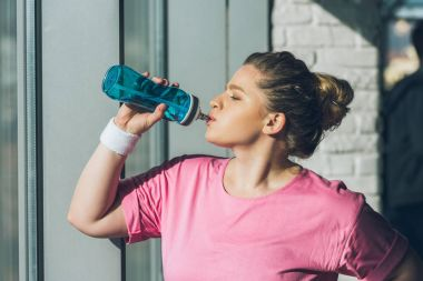 overweight woman drinking water at gym