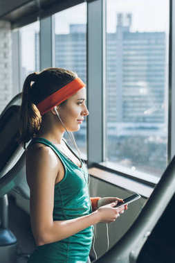 sporty woman using smartphone and earphones at gym while looking at window