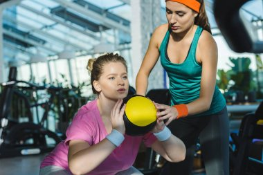 overweight woman training with medicine ball while trainer watching her