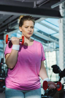 overweight woman training with dumbbells at gym