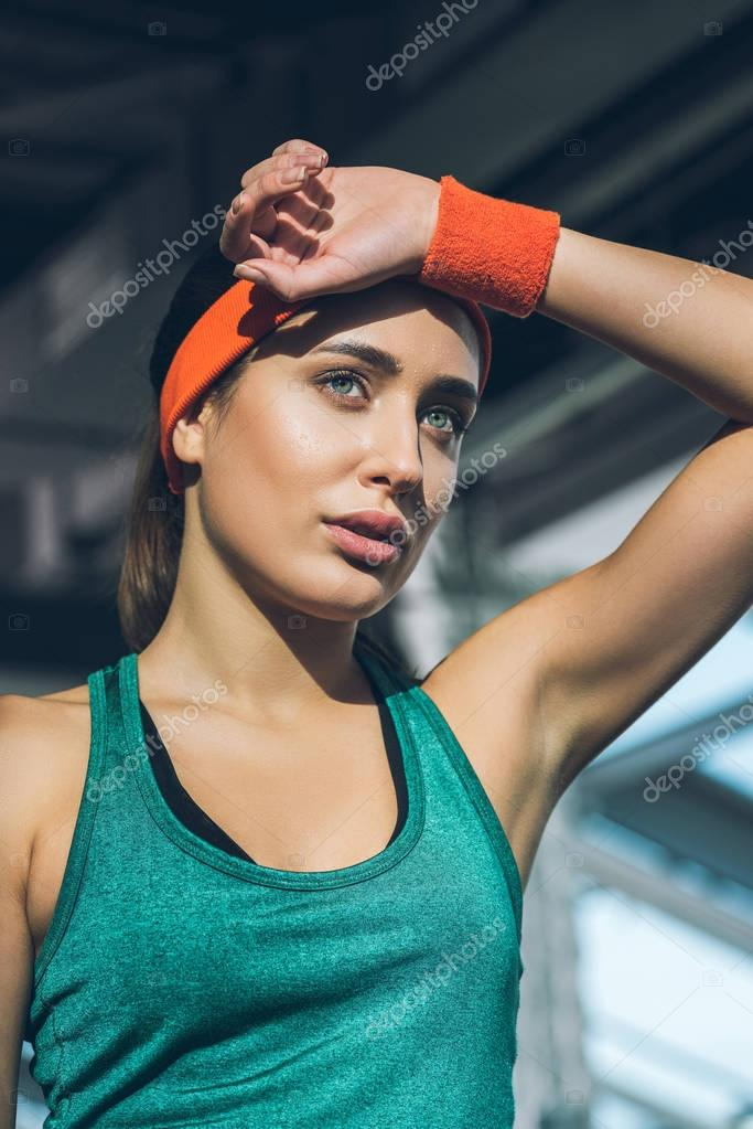 tired sporty woman with hand on forehead at gym