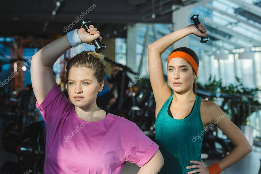 Sporty and overweight women training with dumbbells at gym