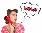 Porträt einer Pin-up-Frau, die auf einem alten Telefon mit einem Wow-Schild im Comic-Stil spricht, isoliert auf weiß