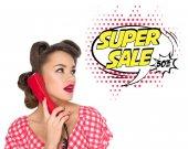 Porträt einer Pin-up-Frau, die auf einem alten Telefon mit einer auf Weiß isolierten Sprechblase im Comic-Stil spricht