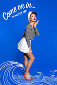 beautiful young woman in sailor shirt and come on in, water is fine inscription isolated on blue