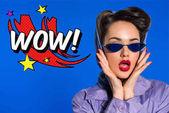 Porträt der stilvolle Frau in Retro-Kleidung und Sonnenbrillen mit Comic-Stil Wow Zeichen isoliert auf blau