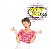 Fotografie Portrait der schönen Frau in Pin-up Kleidung mit Muffins und super Verkauf Sprechblase isoliert auf weiss