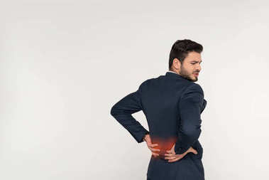 back view of young businessman suffering from backache isolated on grey