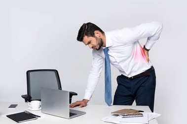 young businessman suffering from backache while leaning at table with laptop