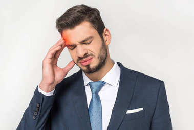 young businessman suffering from headache isolated on grey