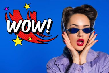 portrait of stylish woman in retro clothing and sunglasses with comic style wow sign isolated on blue