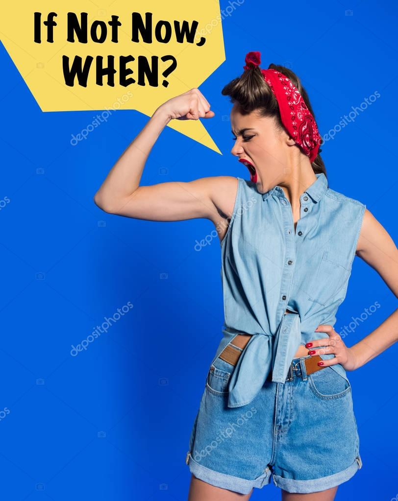 young woman in retro clothing showing muscles and shouting with IF NOT NOW, WHEN? speech bubble isolated on blue