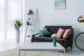 pohled na stylový obývací pokoj s konferenčním stolkem, zelených rostlin a pohovkou