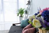 Selektivní fokus pohovky s polštáři ve stylovém obývacím pokoji