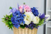 close up view of beautiful springtime bouquet of flowers in straw basket