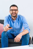 Fotografie portrait of cheerful man changing channels while watching tv at home