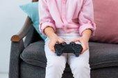 Fotografie Teilansicht des Kind mit Gamepad in Händen Videospiel zu Hause