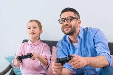 portrait of daughter and father playing video game together at home