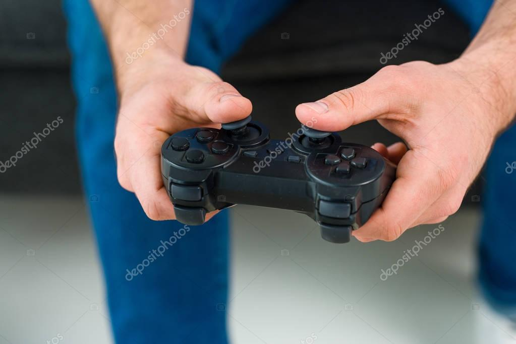 partial view of man playing video game at home