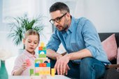 portrait of family building pyramid from colorful blocks at home