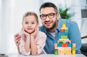 portrait of family and pyramid from colorful blocks at home