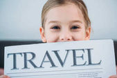 Fotografie obscured view of cute child with travel newspaper