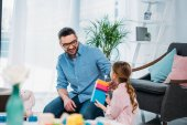 malá dcera a otec hrál s barevnými bloky společně na podlahu doma
