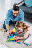 Fotografie little daughter and father playing with colorful blocks together on floor at home