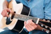 Oříznout záběr člověka hrál na akustickou kytaru doma