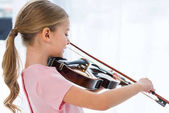 Fotografie side view of cute little child in pink dress playing violin at home
