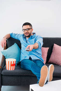 man in eyeglasses resting on sofa and watching tv at home