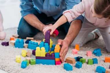 cropped shot of daughter and father playing with colorful blocks together on floor at home