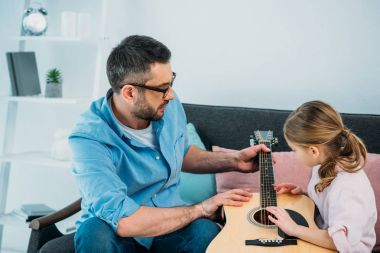 side view of father teaching daughter play guitar at home