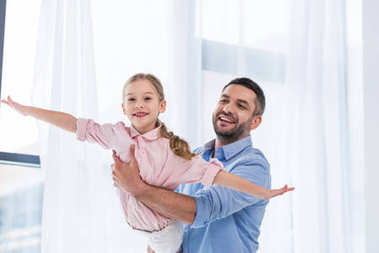 portrait of happy father playing with little daughter at home