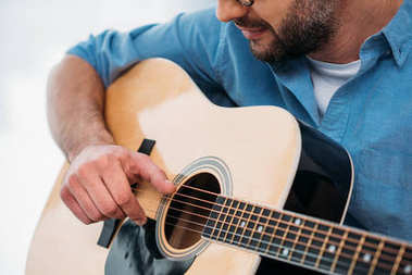 partial view of man playing acoustic guitar at home