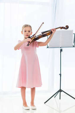 cute little child in pink dress playing violin at home