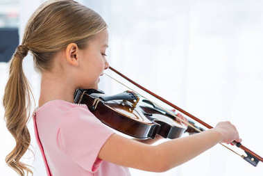 side view of cute little child in pink dress playing violin at home