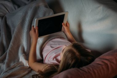 partial view of little kid using tablet in bed at home
