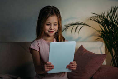portrait of little kid using tablet before going to bed at home