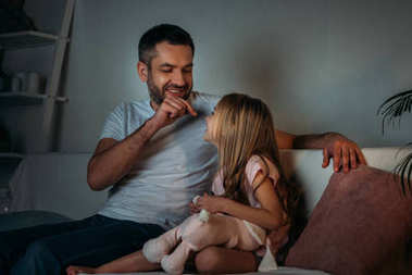 father playing with little daughter while resting on sofa in evening